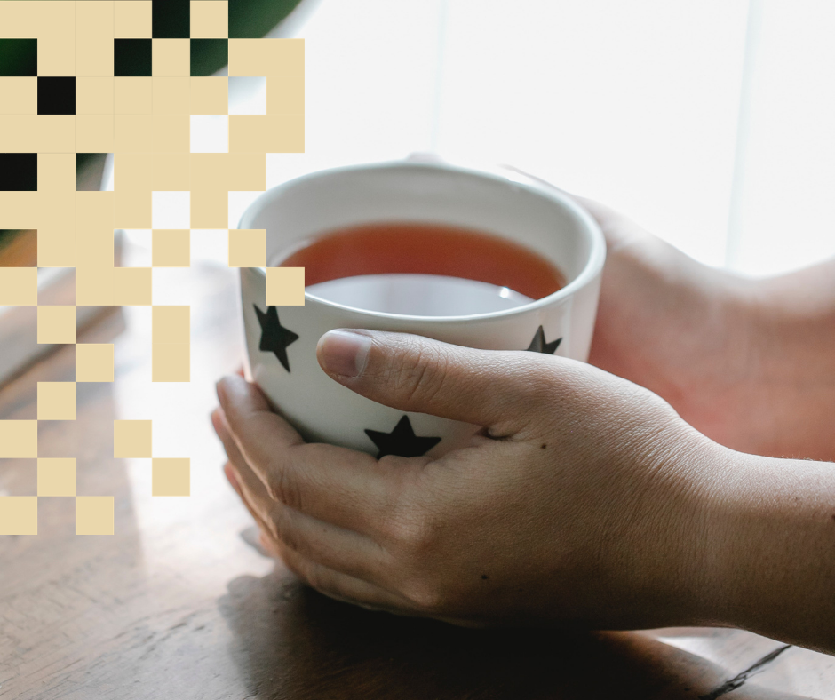 Kädet pitelemässä teekuppia.
