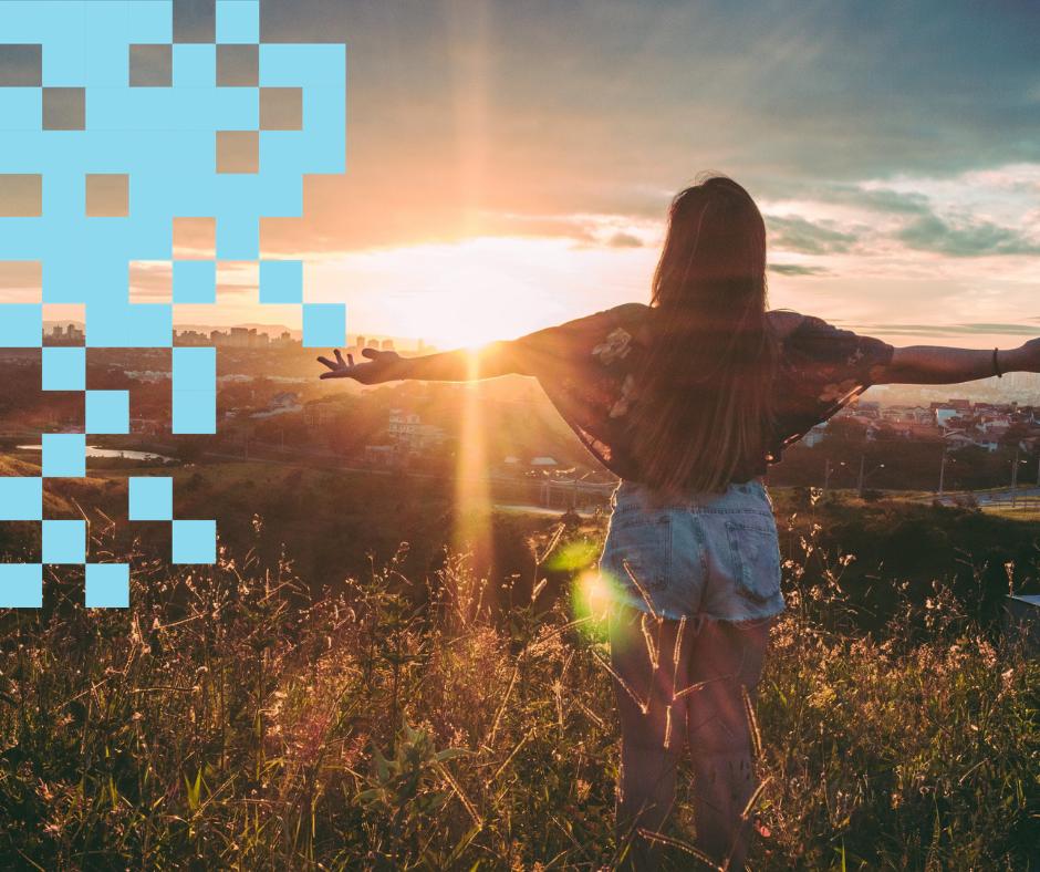 Nuori nainen ihailee auringonlaskua niityllä
