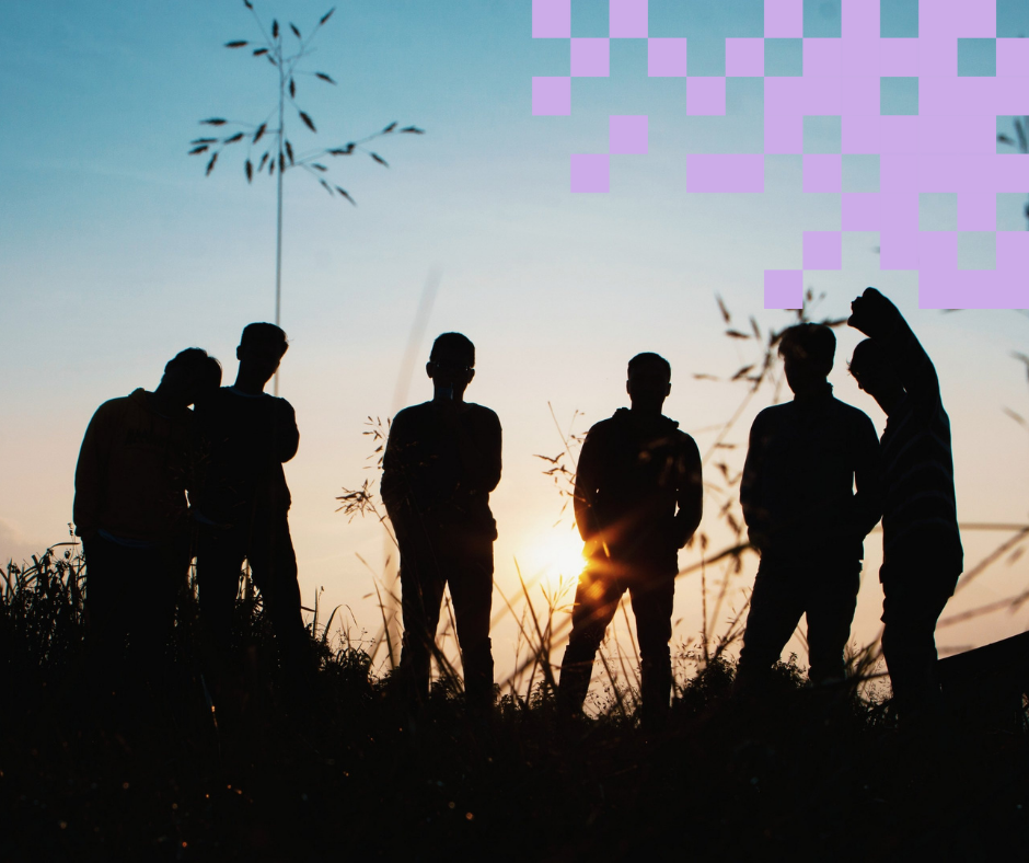 Nuoria ihmisiä viettämässä aikaa yhdessä ulkona auringonlaskun aikaan.